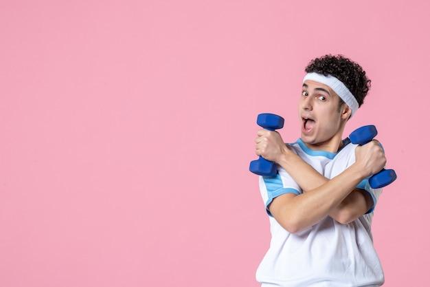 ピンクの壁にダンベルで運動しているスポーツ服の若い男性の正面図