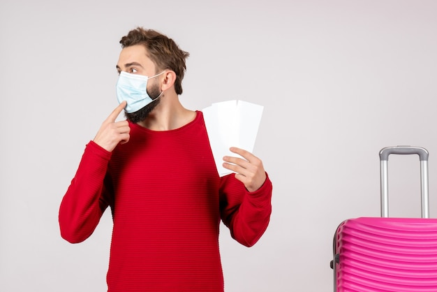 흰 벽에 티켓을 들고 멸균 마스크에 전면보기 젊은 남성 covid 비행기 휴가 감정 바이러스 비행 여행 색상