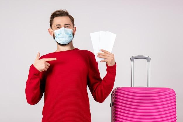 白い壁のcovid-飛行旅行休暇色感情ウイルスのチケットを保持している滅菌マスクの正面図若い男性