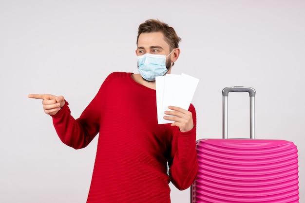 흰 벽 covid- 비행 여행 휴가 바이러스 색상 감정에 티켓을 들고 멸균 마스크에 전면보기 젊은 남성