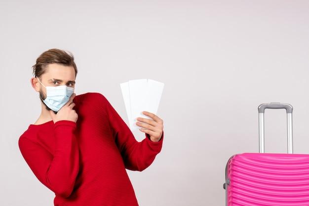 白い壁にチケットを保持している滅菌マスクの正面図若い男性covid-plane休暇感情ウイルス飛行色