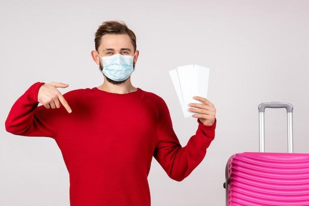 Вид спереди молодой самец в стерильной маске, держащий билеты на белой стене, самолет covid, отпуск, эмоция, вирус, полет, поездка, цвета
