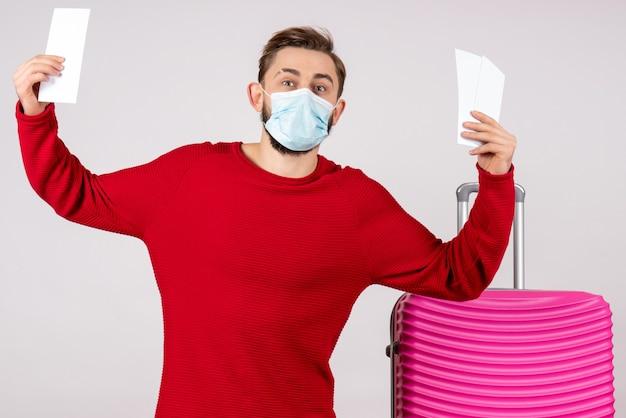 白い壁の航海covid-飛行旅行休暇色感情ウイルスのチケットを保持している滅菌マスクの正面図若い男性