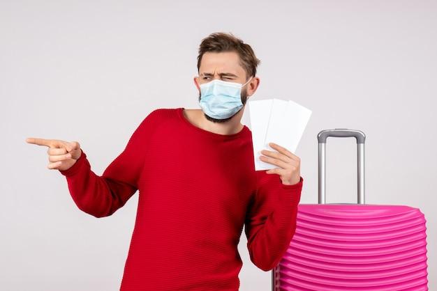 Вид спереди молодой самец в стерильной маске, держащий билеты на белой стене, путешествие, поездка, путешествие, отпуск, цветная эмоция