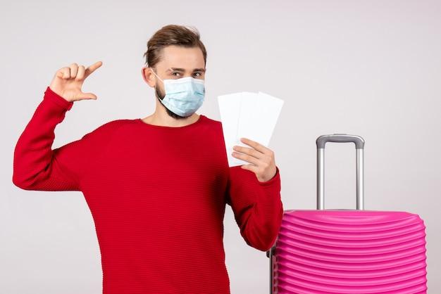 Вид спереди молодой самец в стерильной маске, держащий билеты на белой стене, путешествие, поездка, поездка, полет, отпуск, вирус цветных эмоций