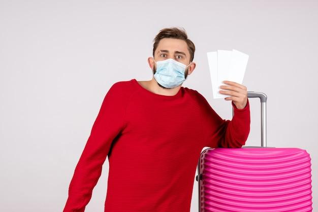 Вид спереди молодой самец в стерильной маске с билетами на белой стене. путешествие, вирус, вирус, отпуск.