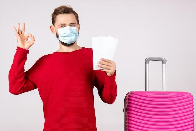 白い壁の航海covid-飛行旅行ウイルス色の感情のチケットを保持している滅菌マスクの正面図若い男性