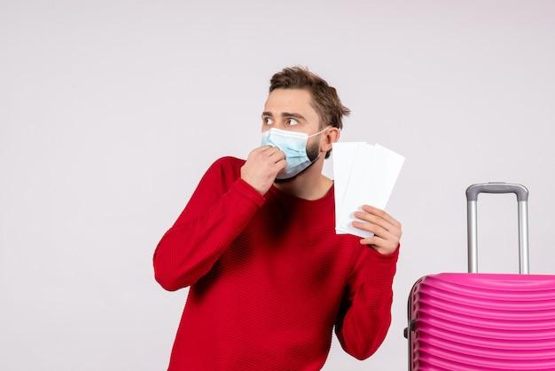 Вид спереди молодой самец в стерильной маске с билетами на белой стене.