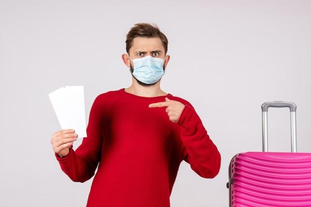 Вид спереди молодой самец в стерильной маске, держащий билеты на белой стене, рейс covid- отпуск цветной эмоции вирусный полет