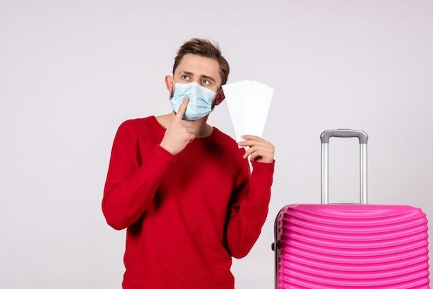 Вид спереди молодой самец в стерильной маске, держащий билеты, думающий на белой стене, путешествие, поездка, поездка, поездка, отпуск, цветной вирус эмоций