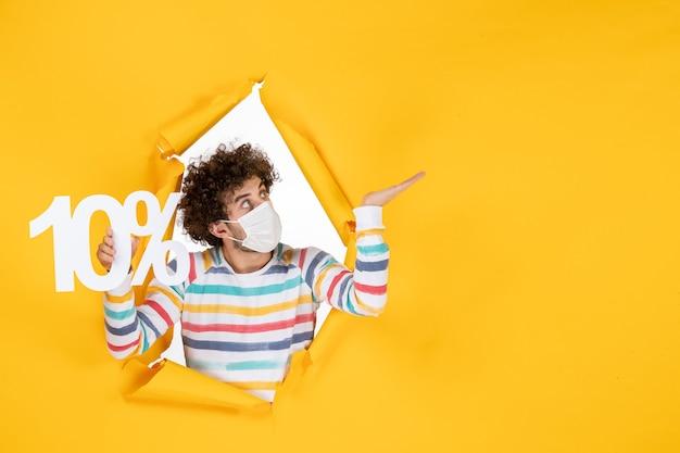 黄色の写真健康コロナウイルスパンデミック販売に書き込みを保持している滅菌マスクの正面図若い男性