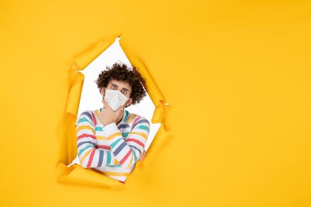 Вид спереди молодой самец в стерильной маске в позе мышления на желтой фотографии здоровья человека пандемического вируса