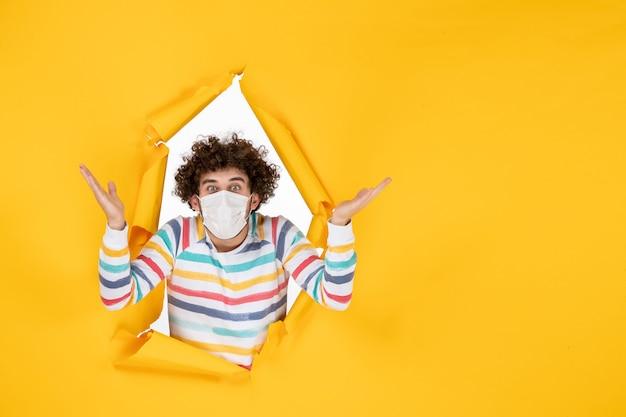 黄色の健康色covidパンデミックウイルス人間の写真の滅菌マスクの正面図若い男性