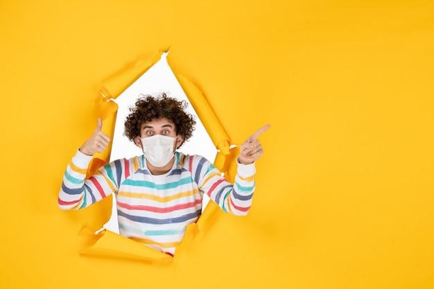 Вид спереди молодой самец в стерильной маске на желтом разорванном цвете covid- здоровье человека фото пандемический вирус