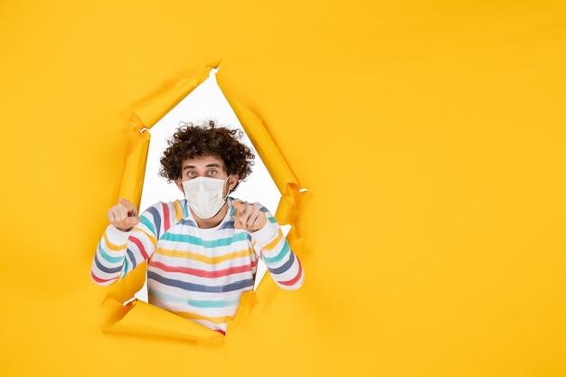 黄色のcovid-人間のパンデミックウイルス写真の滅菌マスクの正面図若い男性