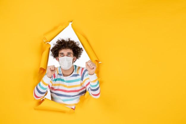 黄色の健康色covidコロナウイルスヒト写真パンデミックの滅菌マスクの正面図若い男性