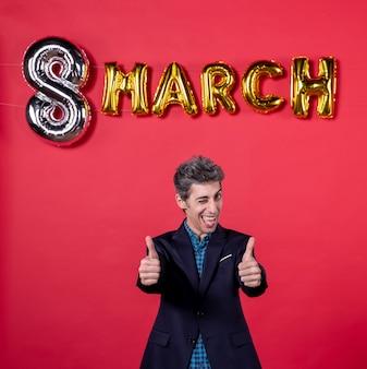 赤い背景の3月の装飾とスーツの正面図若い男性情熱女性の日フェミニンなショッピング休日の平等