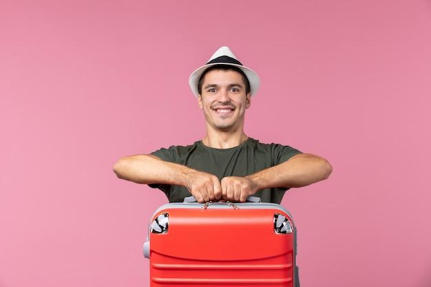 ピンクのスペースに赤いバッグを運ぶ休暇中の若い男性の正面図