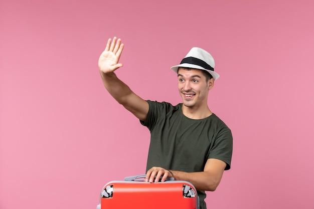 ピンクのスペースに手を振って赤いバッグを運ぶ休暇中の若い男性の正面図