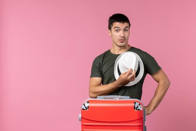 ピンクのスペースに帽子を保持している休暇中の若い男性の正面図