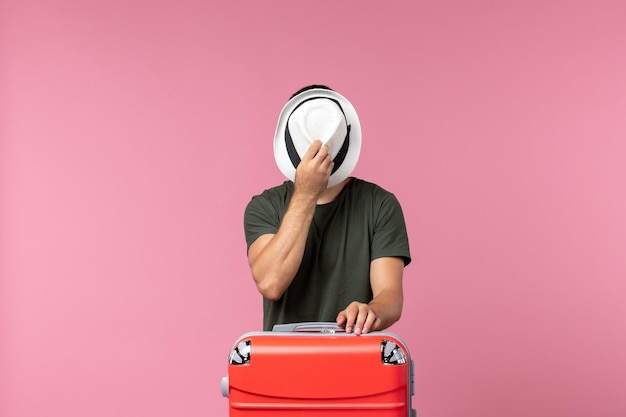 핑크 책상에 그의 모자를 들고 휴가에 전면보기 젊은 남성