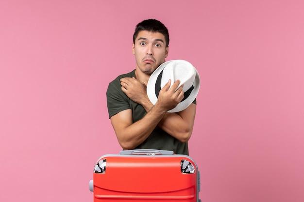 ピンクのスペースに彼の帽子を保持している休暇中の若い男性の正面図