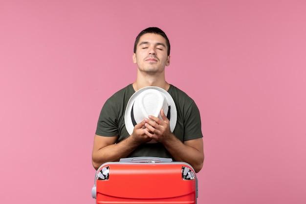 Вид спереди молодой самец в отпуске, держа шляпу на розовом пространстве