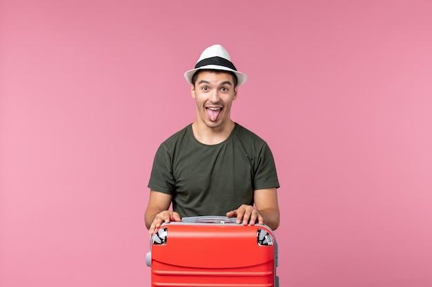淡いピンクの空間で休暇中の若い男性の正面図