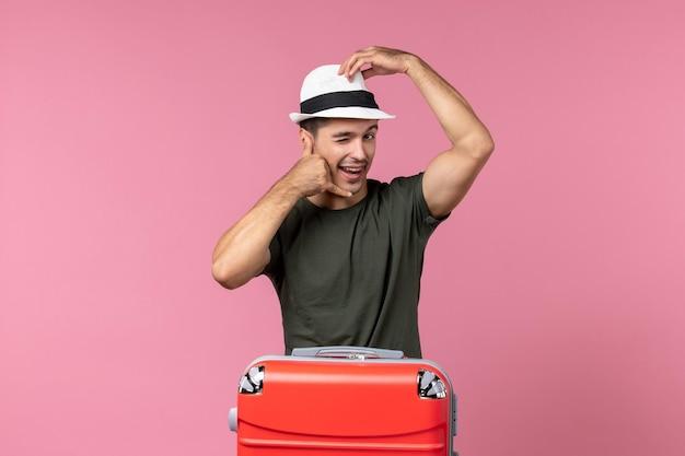 ピンクの机の上に帽子をかぶって休暇中の若い男性の正面図