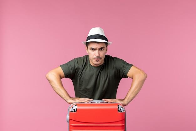 Вид спереди молодой самец в отпуске с красной сумкой на розовом пространстве