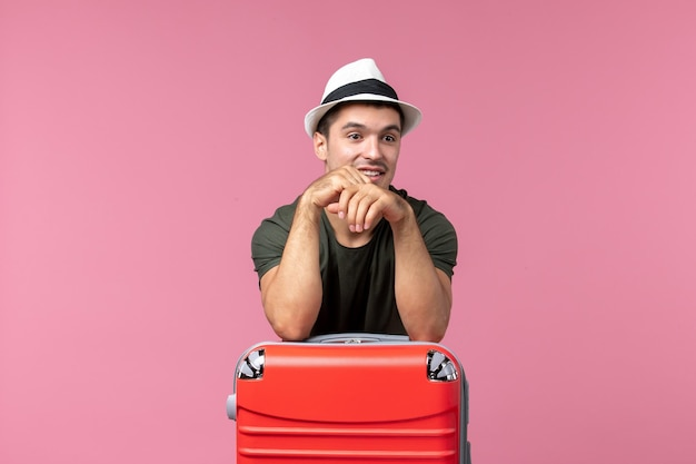 분홍색 공간에 그의 빨간 가방과 함께 휴가에 전면보기 젊은 남성