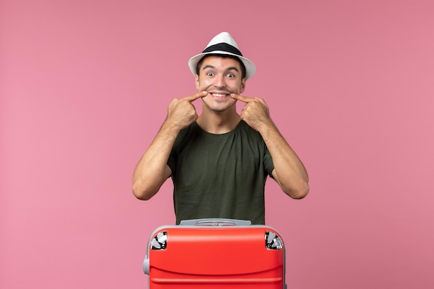ピンクのスペースに彼の赤いバッグと休暇中の若い男性の正面図