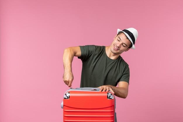 ピンクの机の上の赤いバッグと休暇中の若い男性の正面図