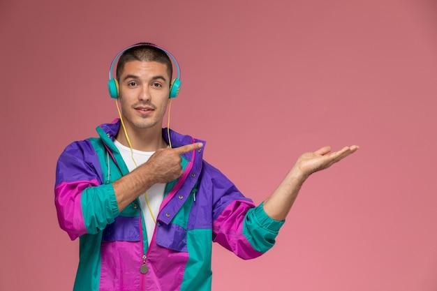 ピンクの背景で音楽を聞いて白いシャツのカラフルなコートで正面の若い男性