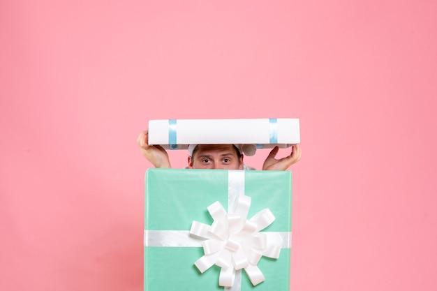 ピンクの背景にプレゼントの中の白いシャツの正面図若い男性