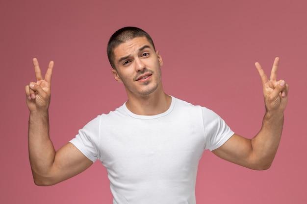 Вид спереди молодой мужчина в белой рубашке показывает знаки победы на розовом фоне