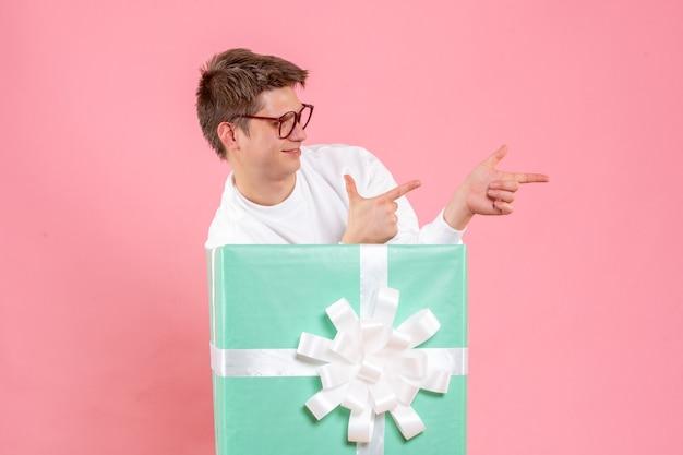 ピンクの背景にプレゼントと白いシャツの正面図若い男性