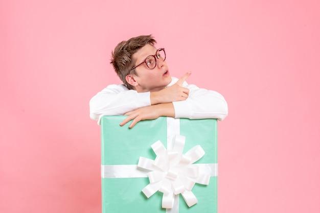 Вид спереди молодой мужчина в белой рубашке с подарком на розовом фоне