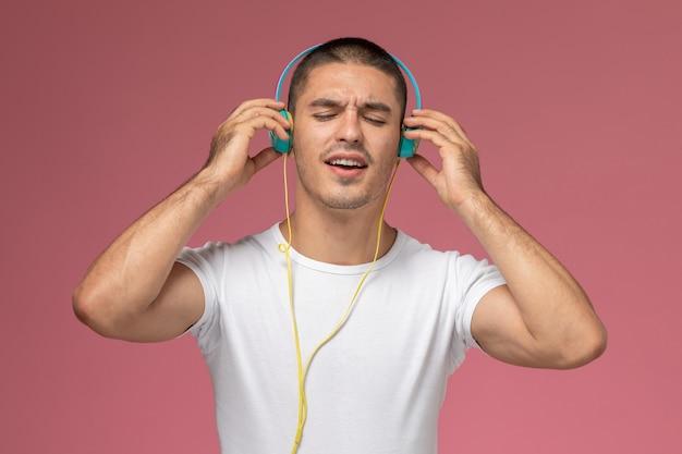 Вид спереди молодой мужчина в белой футболке, слушающий музыку через наушники на розовом фоне