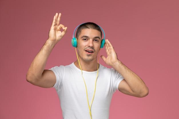 Молодой мужчина в белой футболке, вид спереди, слушает музыку в наушниках на светло-розовом фоне