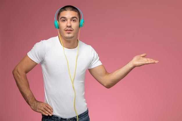 Молодой мужчина в белой футболке, вид спереди, слушает музыку в наушниках на светло-розовом столе