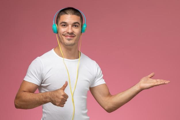 Вид спереди молодого мужчины в белой футболке, слушающего музыку в наушниках, улыбаясь на светло-розовом фоне
