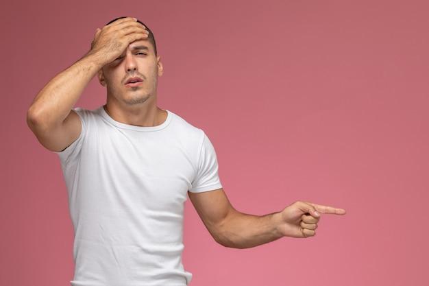 분홍색 배경에 dissapointed 식으로 포즈를 취하는 흰색 티셔츠에 전면보기 젊은 남성