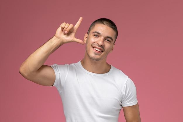 Вид спереди молодой мужчина в белой футболке позирует с поднятым пальцем на розовом фоне