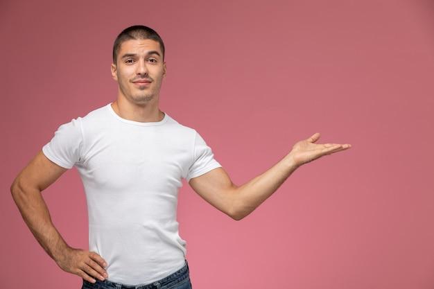 ピンクの背景に上げられた手と手のひらでポーズをとって白いtシャツで正面の若い男性