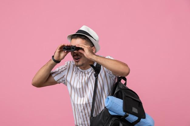Вид спереди молодой мужчина в белой футболке с помощью бинокля на розовом фоне