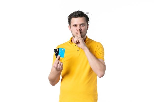 전면보기 흰색 배경에 은행 카드 한 켤레를 들고 노란색 셔츠에 젊은 남성 유니폼 작업 작업자 돈 색상 인간의