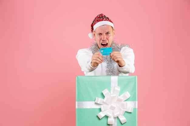 ピンクの背景に銀行カードを保持しているプレゼントの中の正面図若い男性