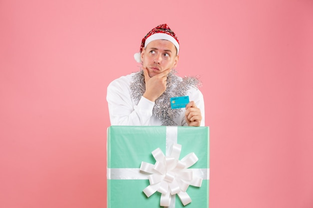 Front view young male inside present holding bank card thinking on pink background