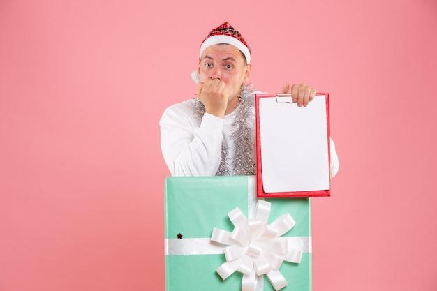 ピンクの背景にファイルノートを保持しているプレゼントの中の正面図若い男性